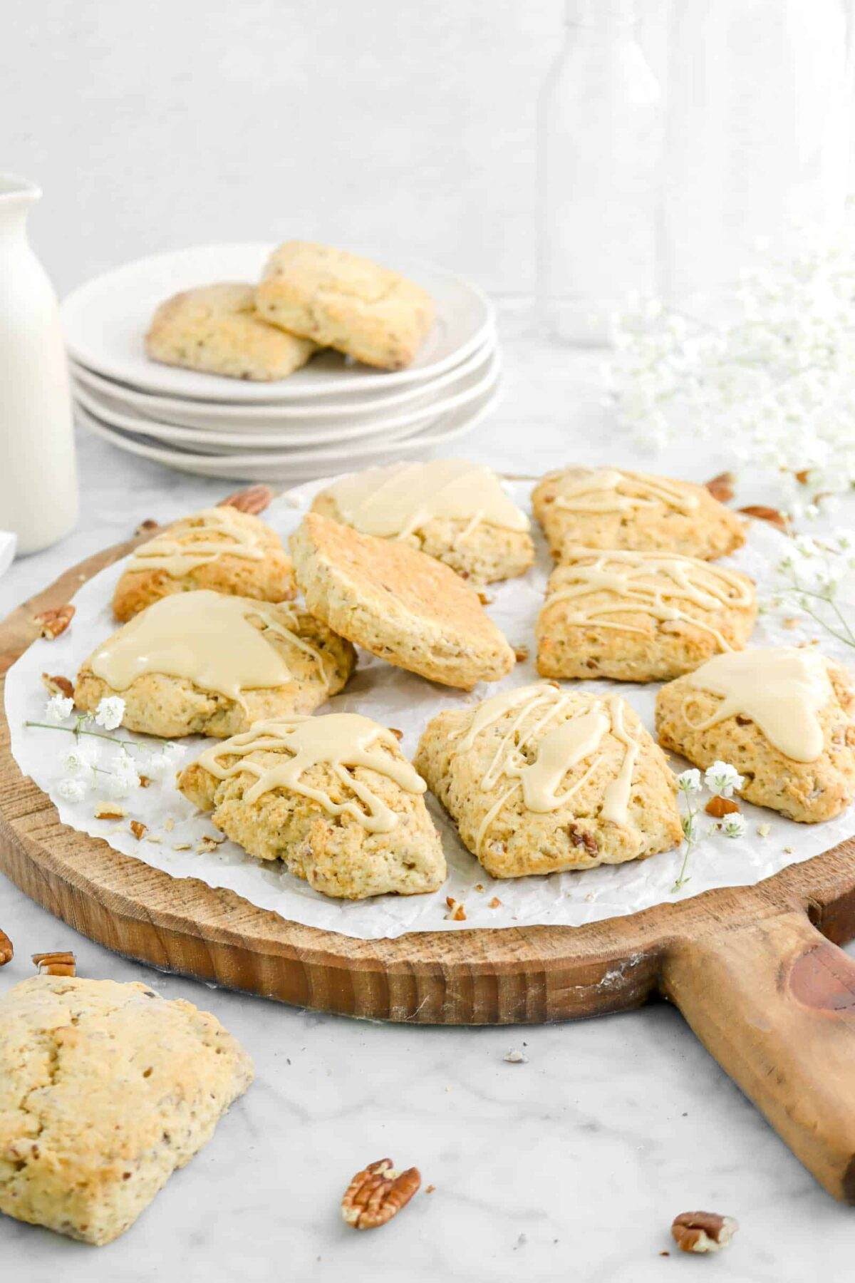 side shot of maple pecan scones on wood serving board with flowers and stacked plates