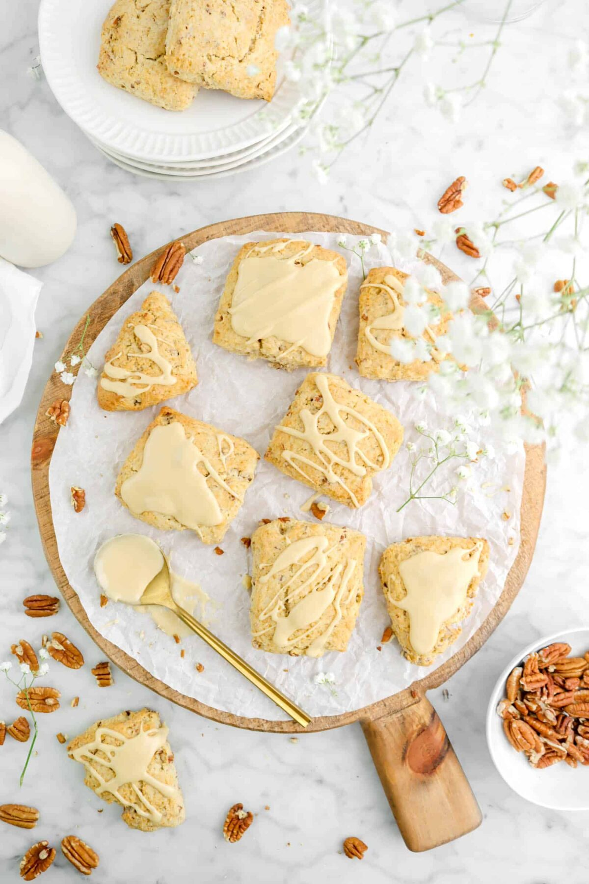scones on wood serving board with flowers above, a gold spoon with icing and whole pecans scattered around