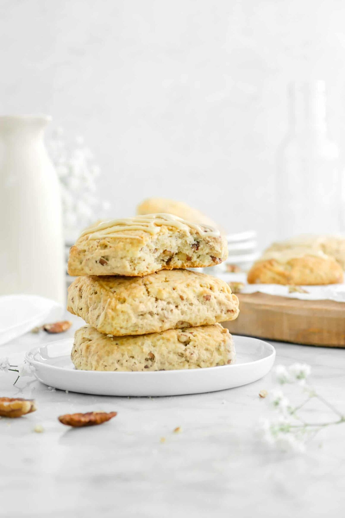 three stacked scones on white plate with a bite missing and flowers around