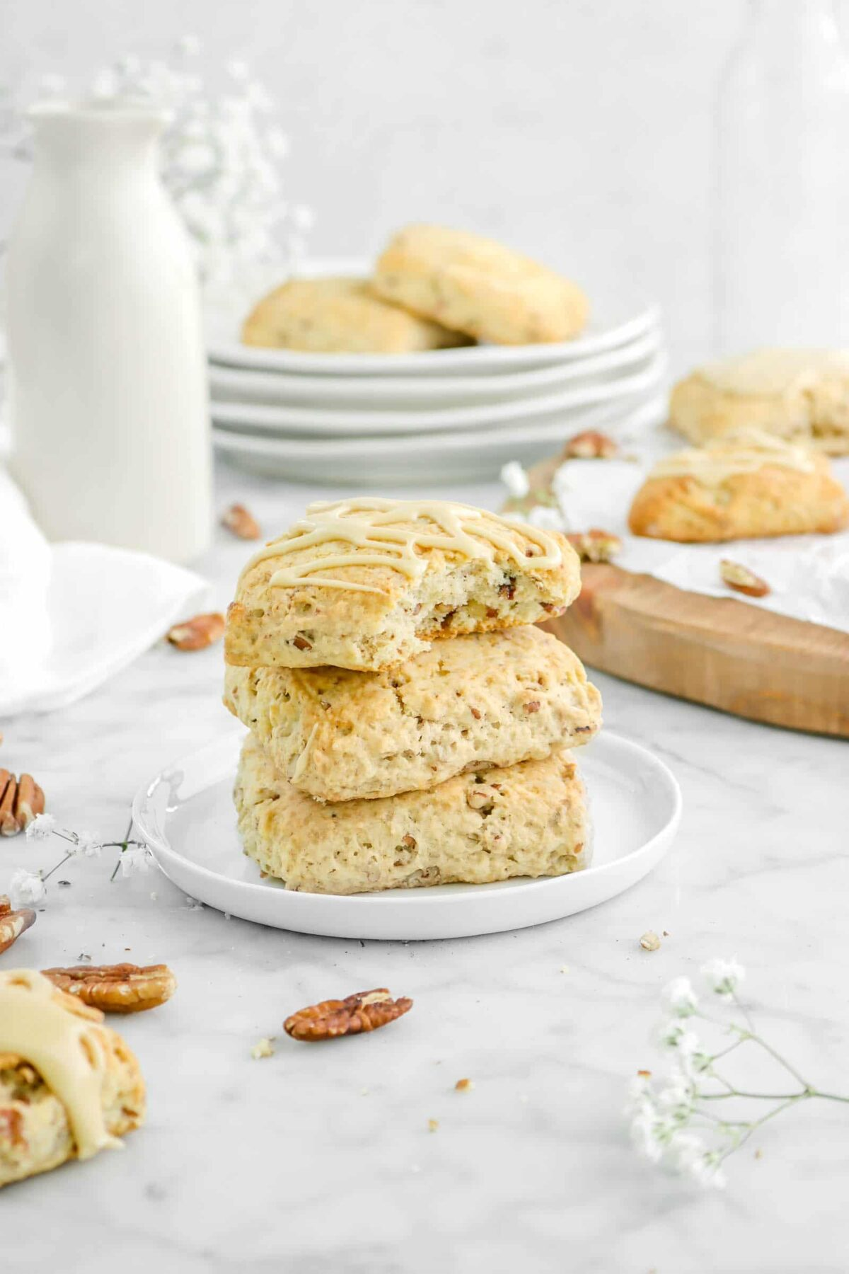 stacked scones on white plate with a bite missing from one with more scones behind, flowers, pecans, and stacked plates