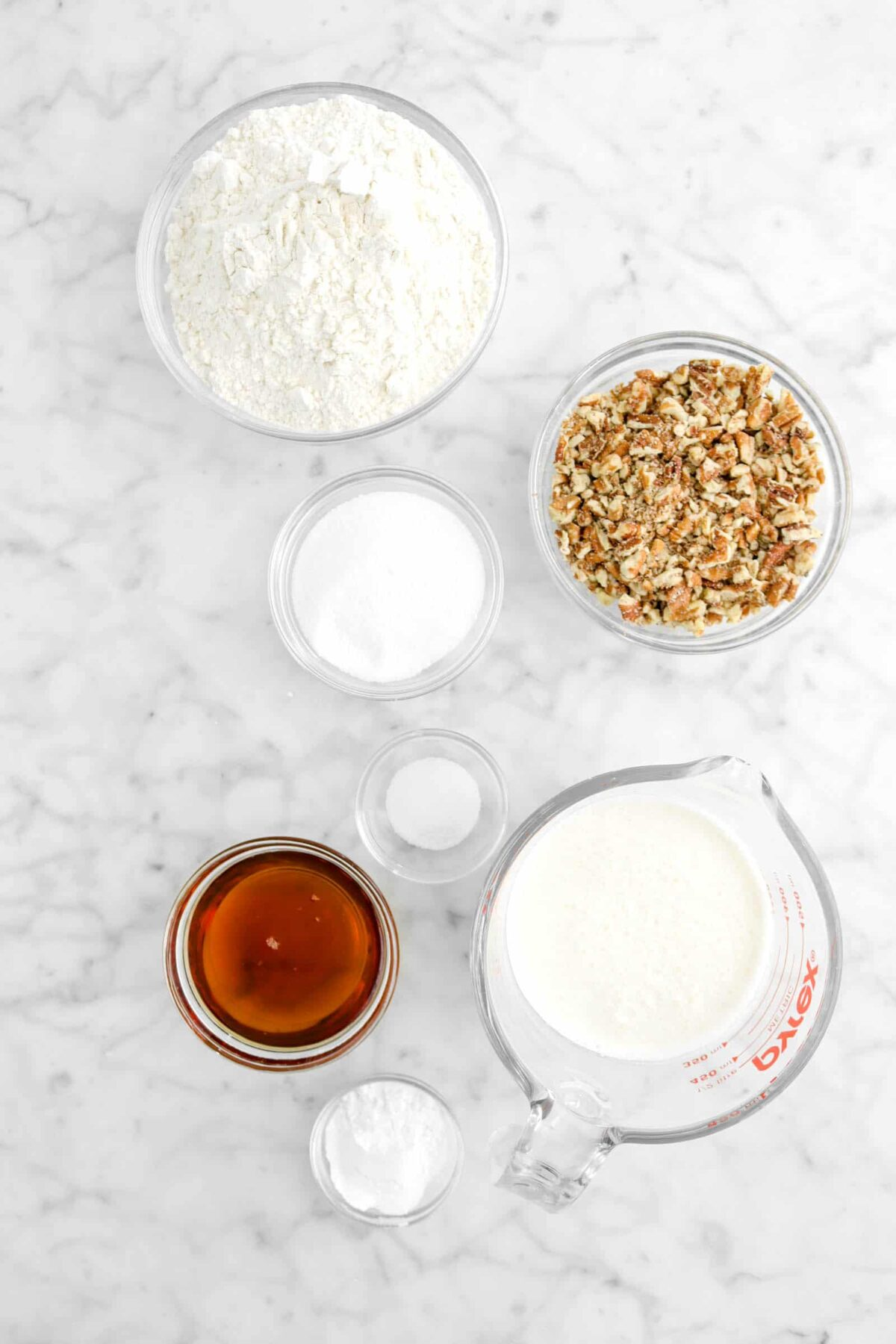 flour, chopped pecans, sugar, salt, maple syrup, milk, and baking powder in glass bowls