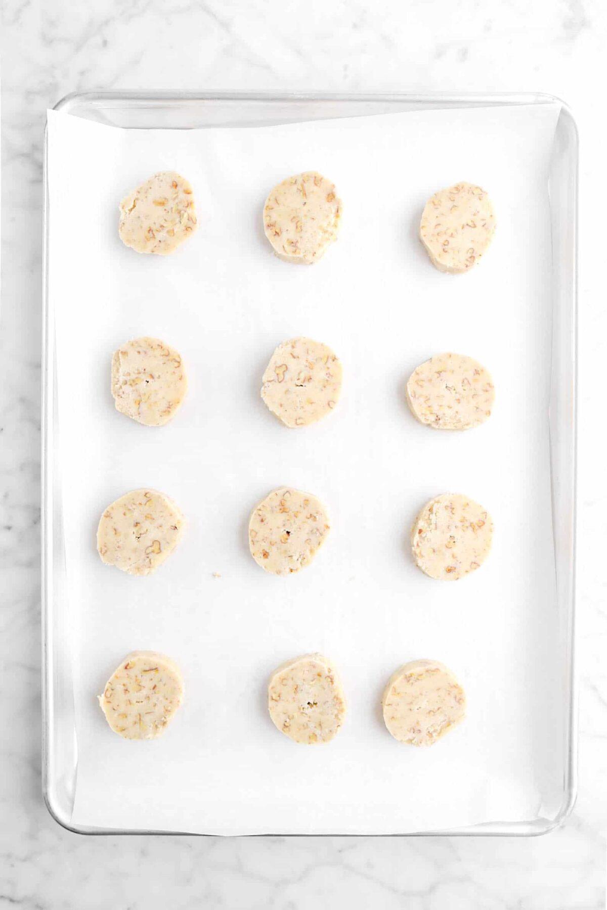 twelve cookies on a lined sheet pan