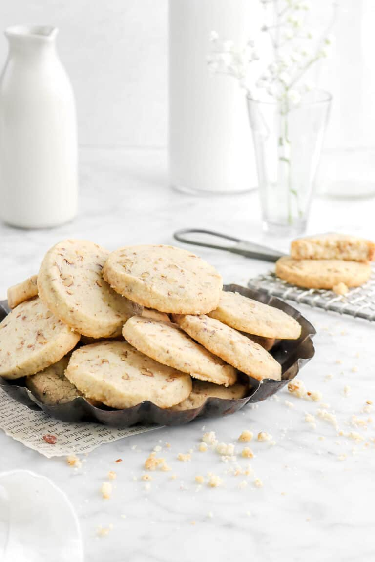 pecan shortbread cookies stacked on pie pan with cookie crumbs around, a cookie behind, flours, and glass of milk