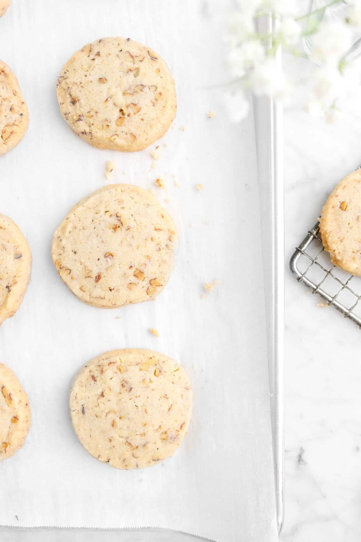 overhead shot of cookies on sheet pan with flowers overhead