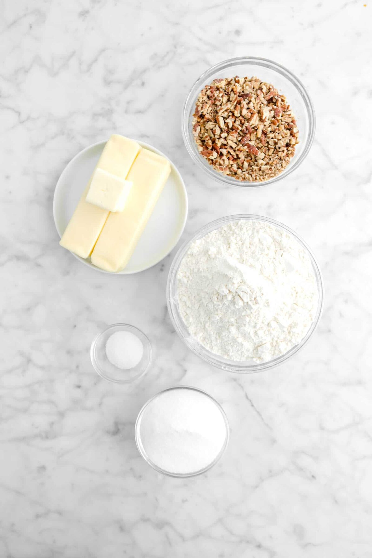 chopped pecans, butter, flour, salt, and sugar on marble counter
