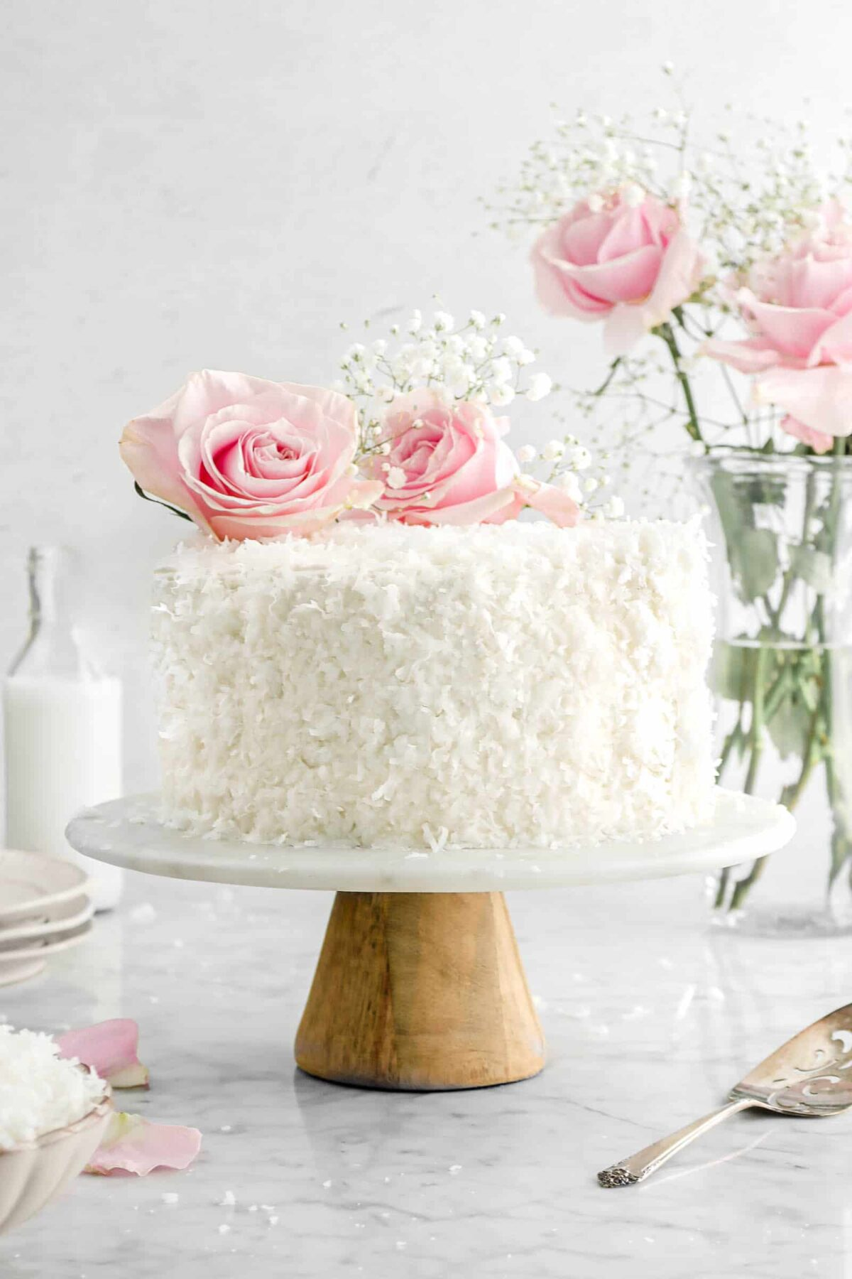 coconut cake on cake plate with flowers on top, flowers behind, a glass of milk, and paltes