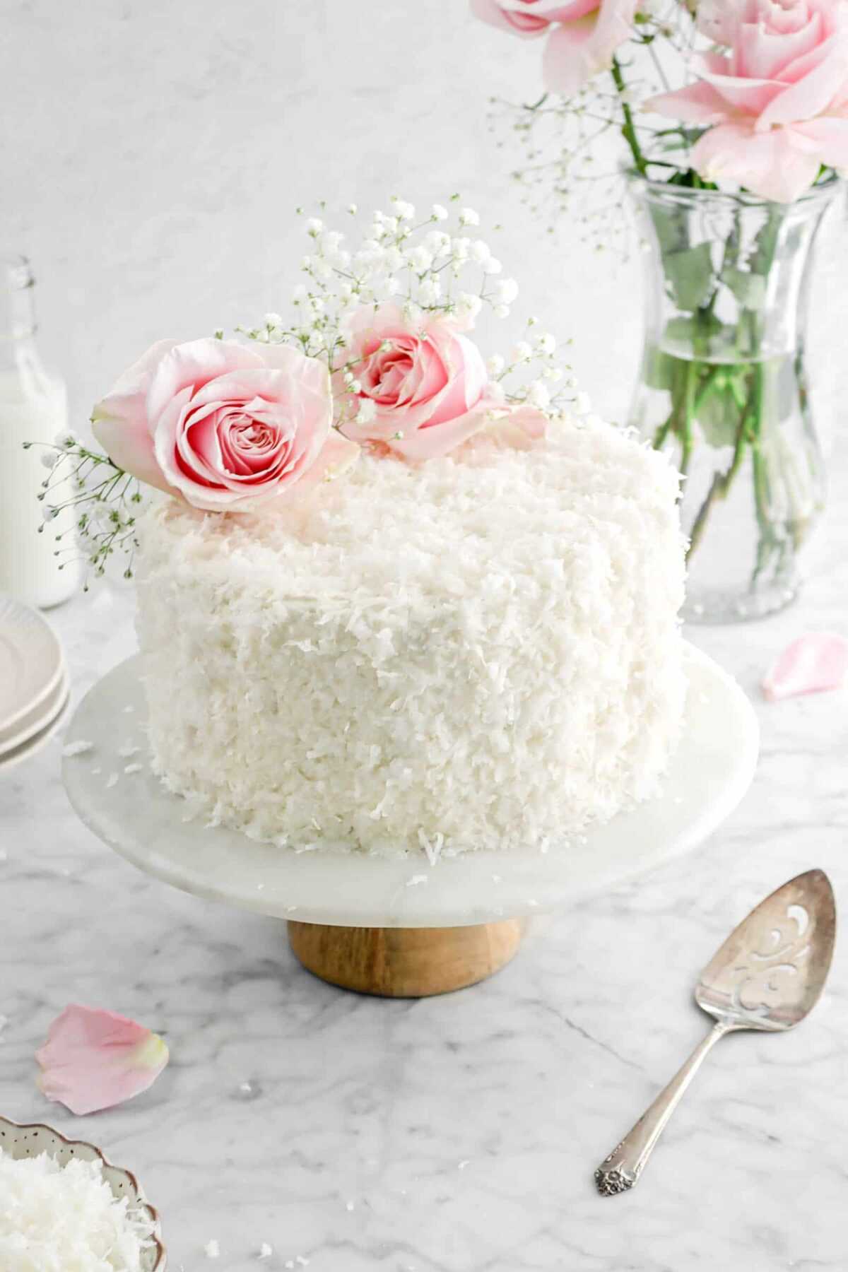 coconut cake with flowers on a cake plate with a cake knife and more flowers behind