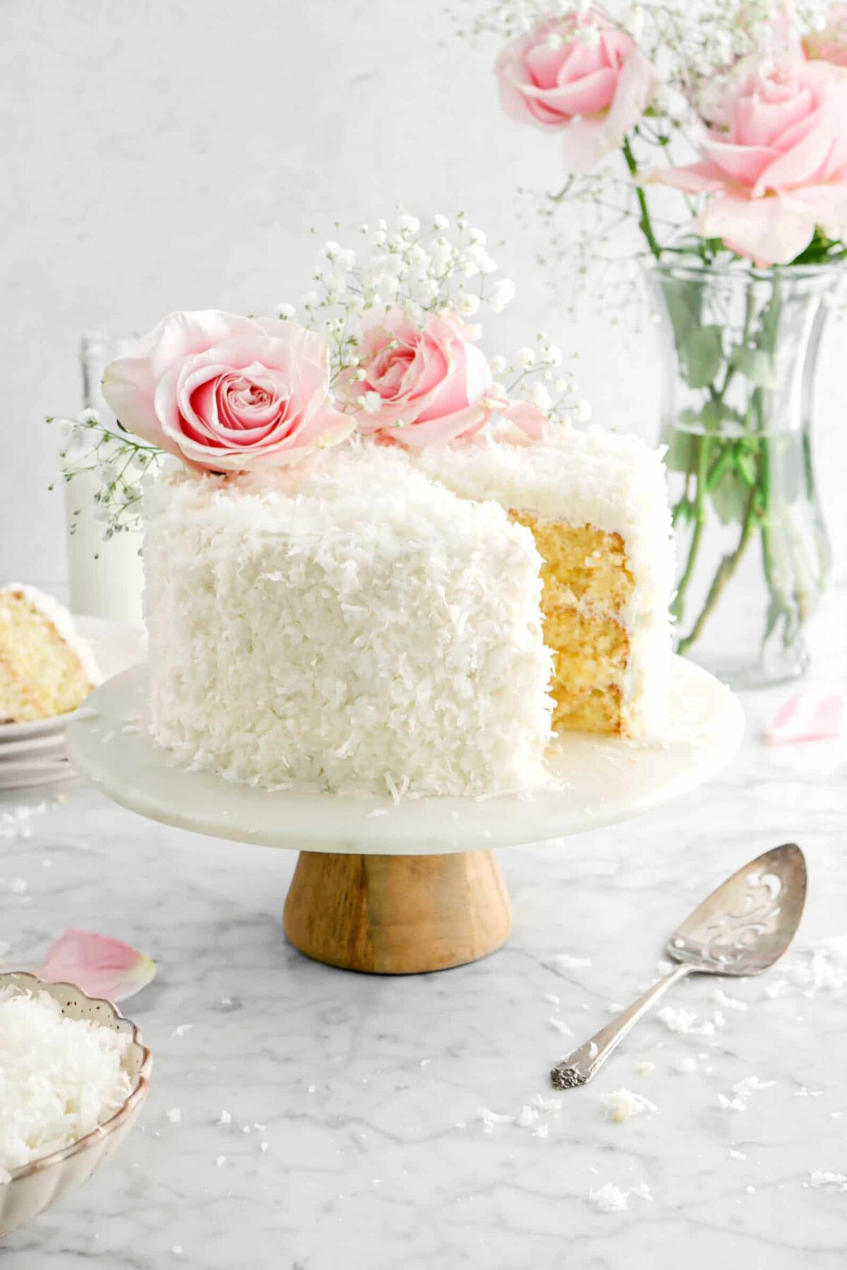 coconut cake with slice behind, roses on top and behind the cake, a bowl of shredded coconut in front, and a cake knife