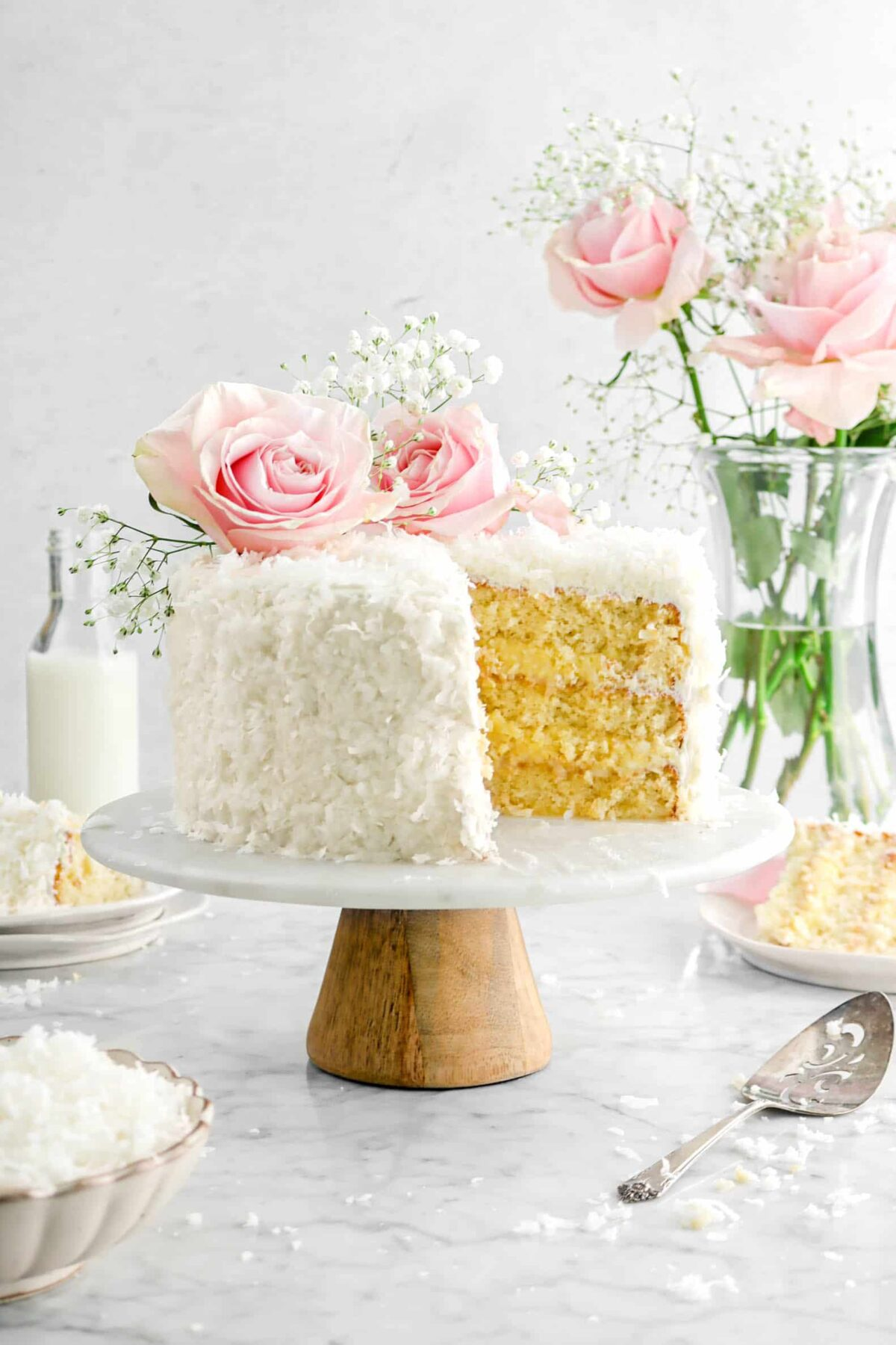 coconut cake with two slices behind, roses on top, and a bowl of coconut shreds
