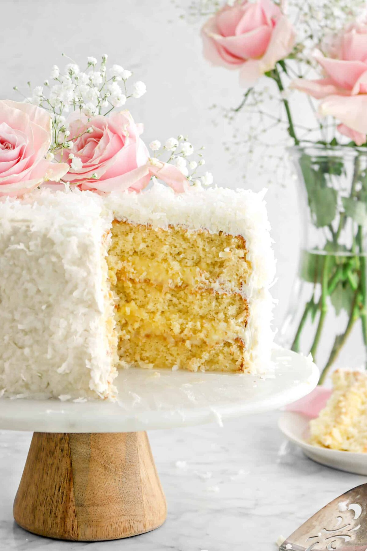 close up of sliced coconut cake on cake plate