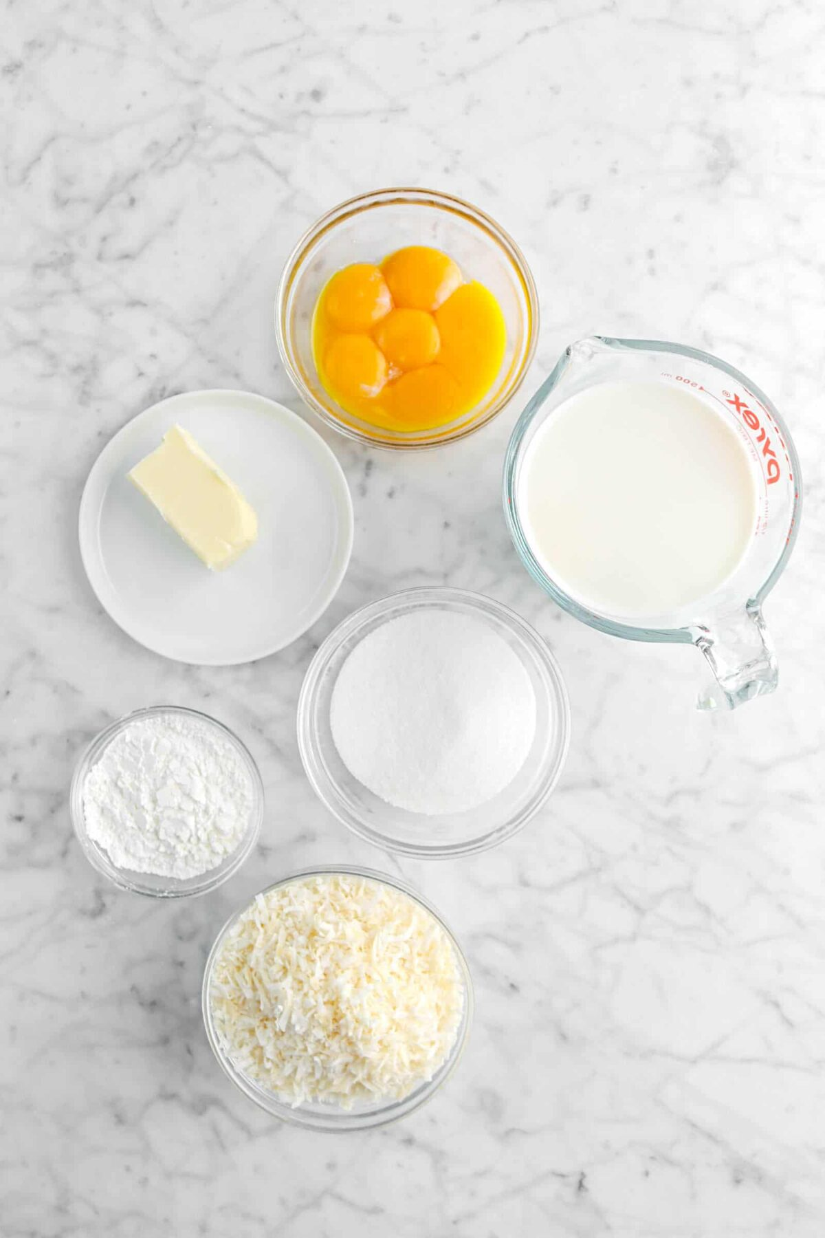 egg yolks, milk, butter, sugar, corn starch, and shredded coconut on marble counter