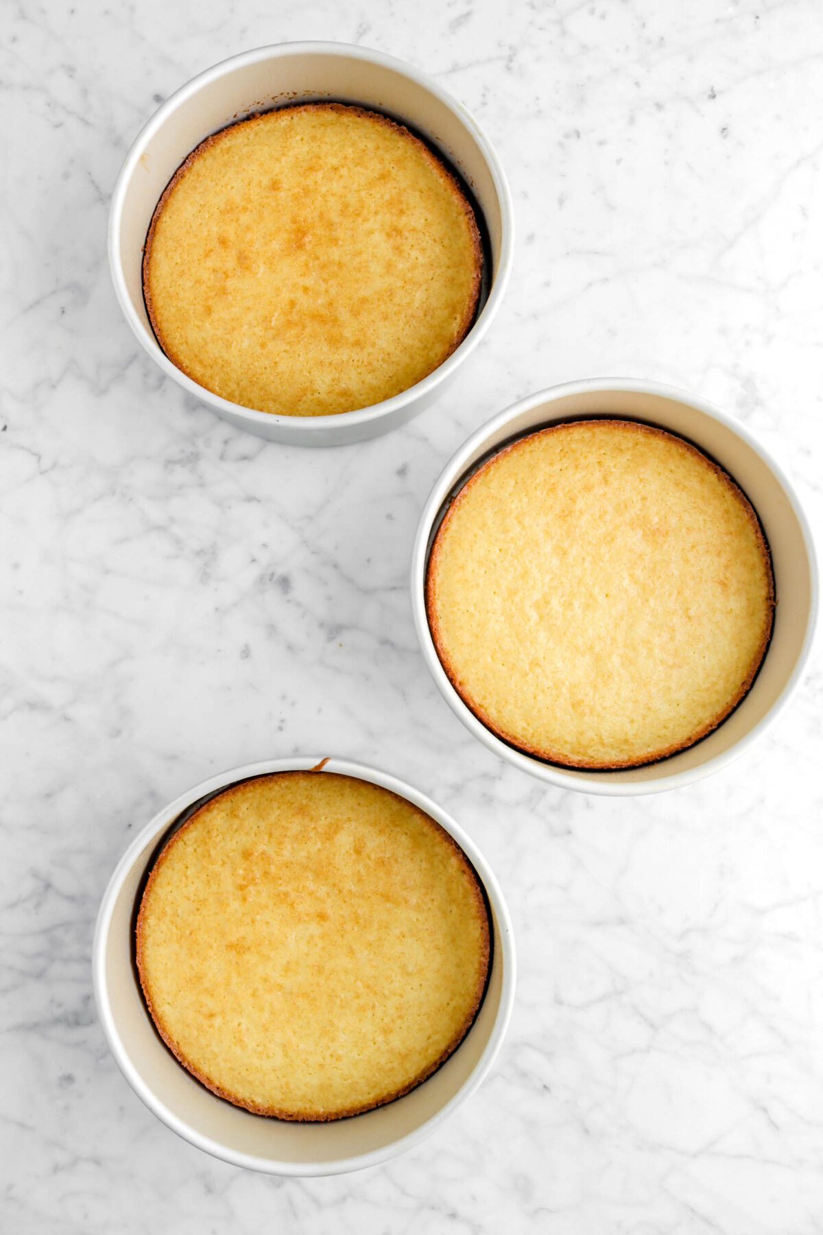 three baked cake layers in pans
