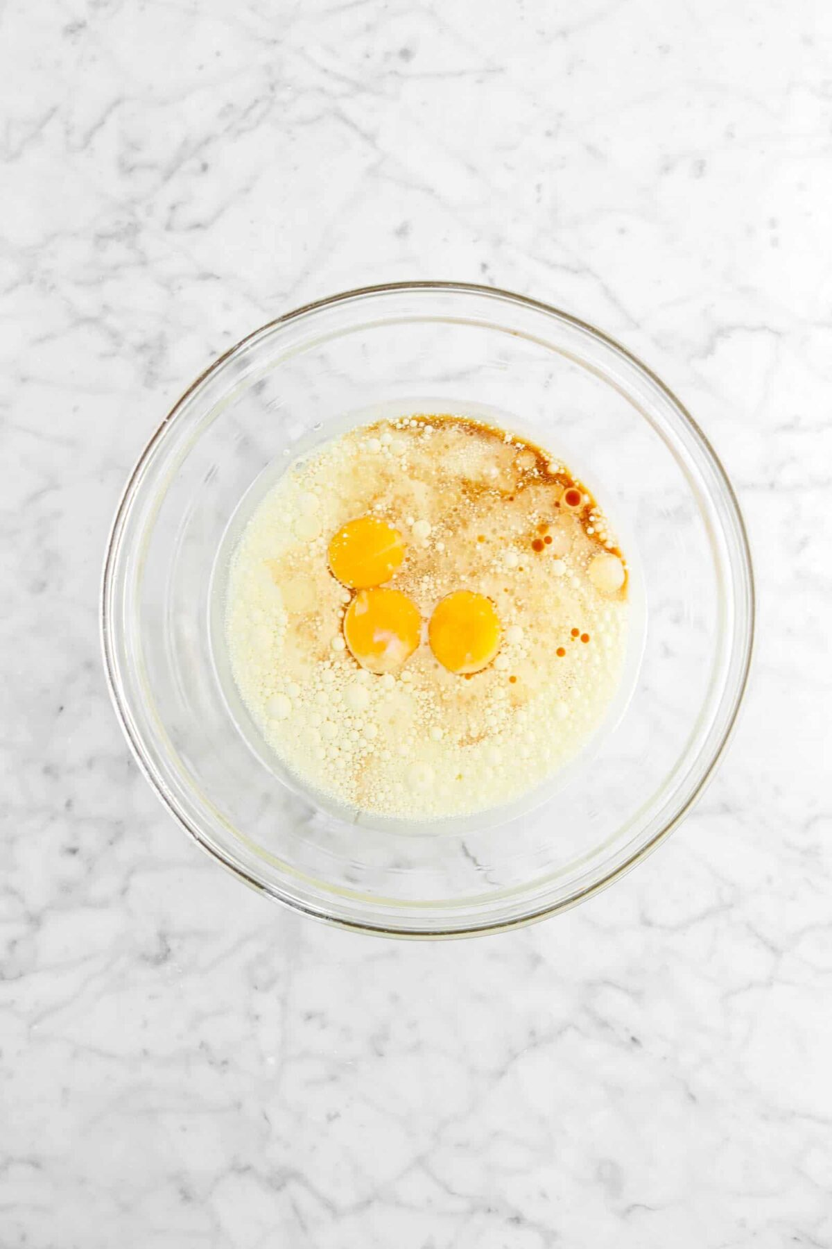 egg yolks, vanilla, milk, vanilla, and oil in glass bowl