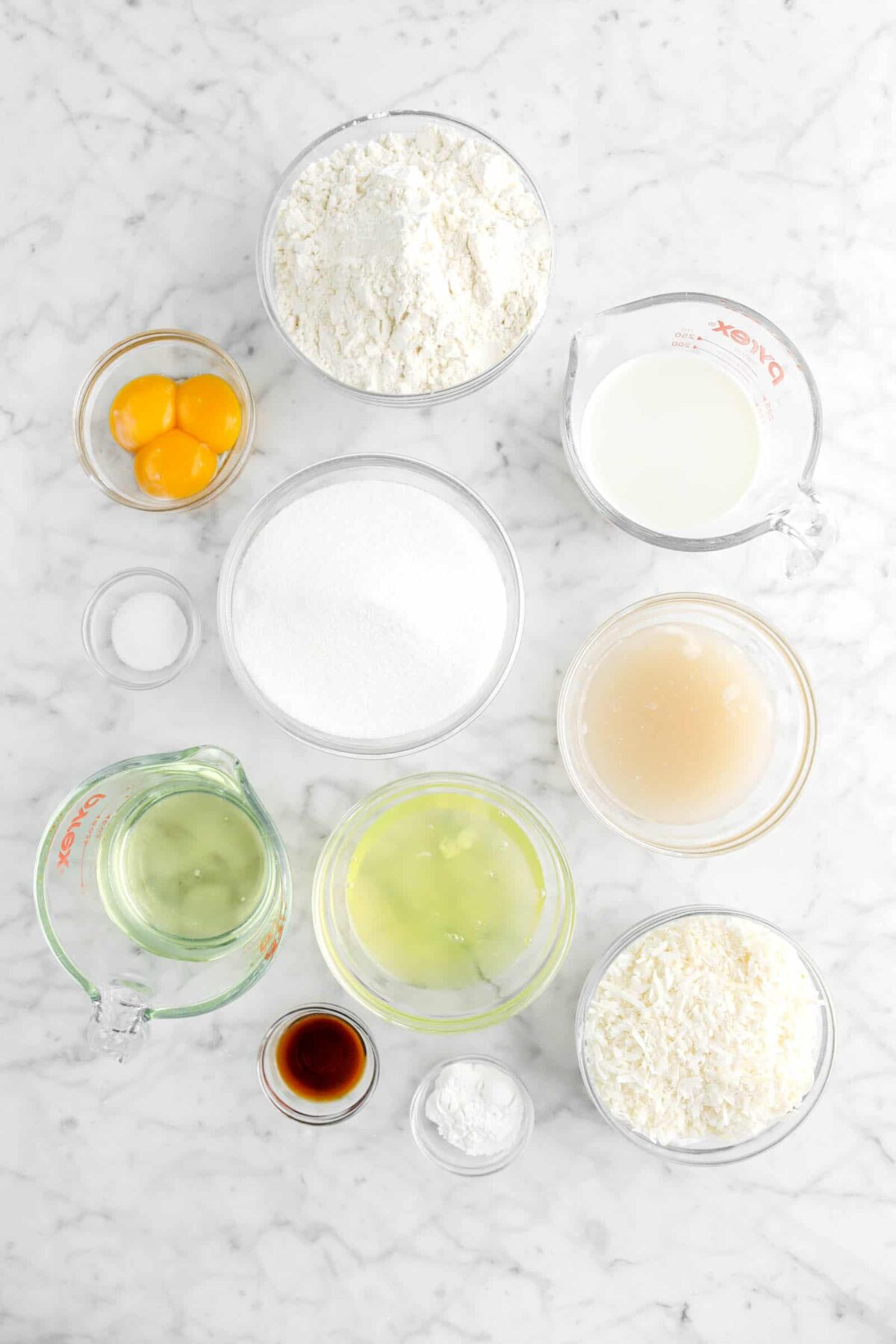 flour, milk, egg yolks, sugar, salt, cream of coconut, egg whites, vegetable oil, vanilla, baking powder, and shredded coconut on marble counter