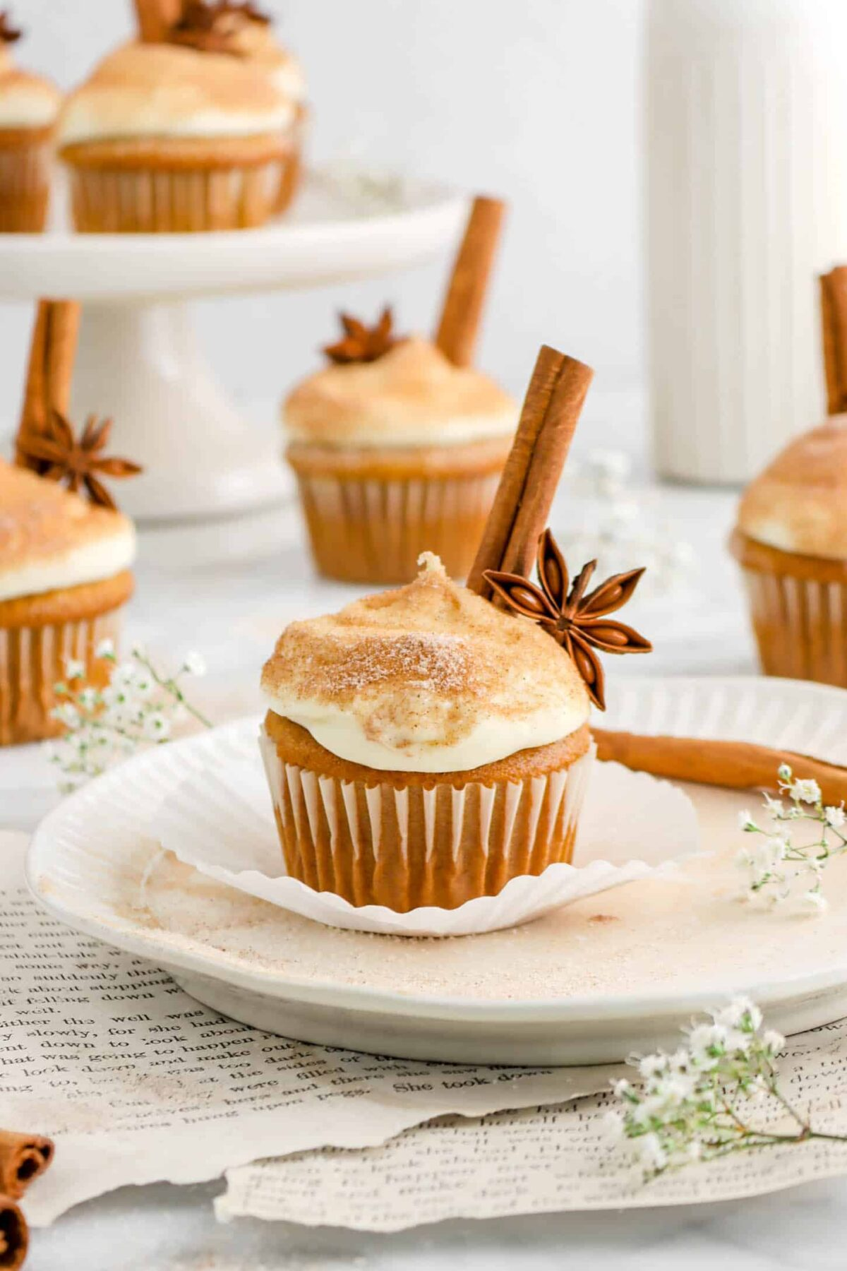 pumpkin cupcake with star anise and cinnamon stick on white plate, book pages underneath, more cupcakes behind, and flowers