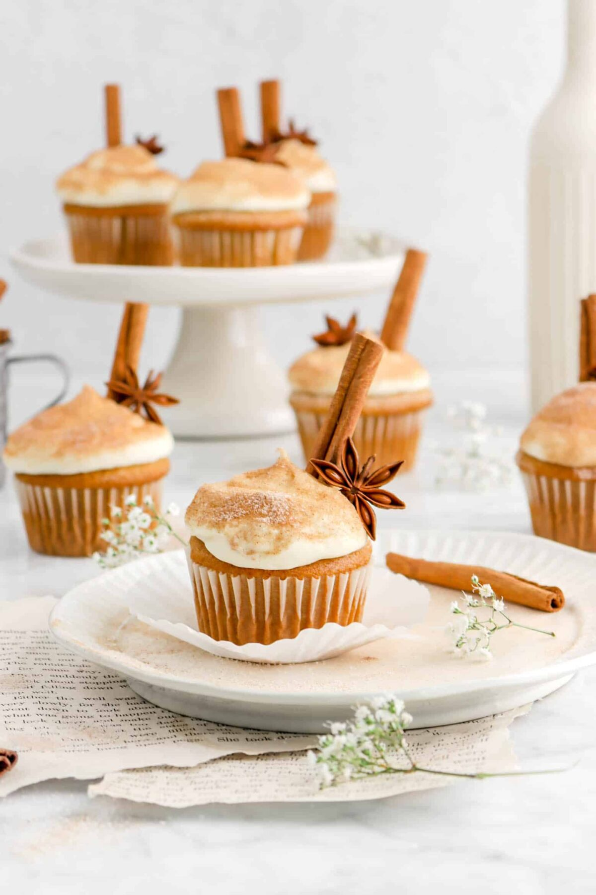 gluten free cupcake on plate with whole spices, flowers, and more cupcakes behind