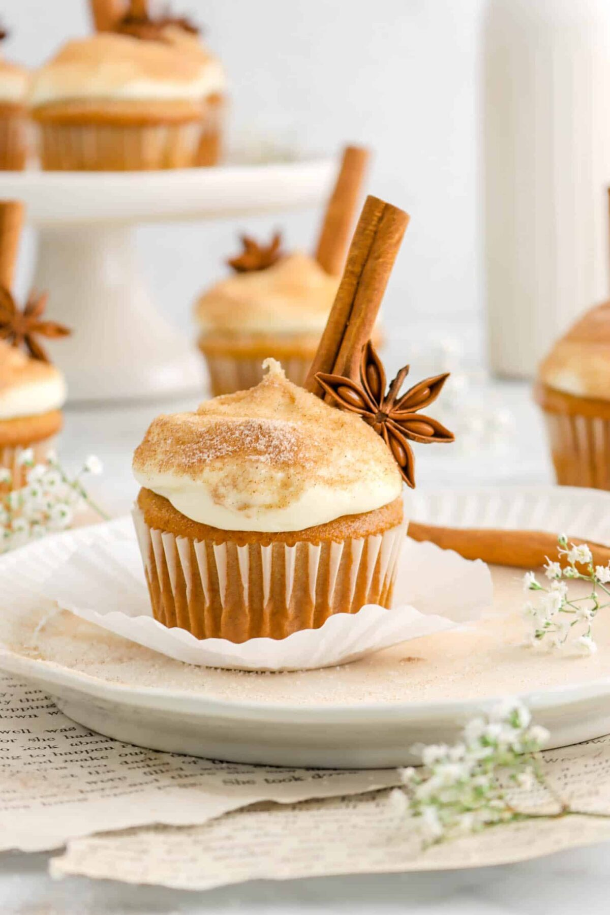 pumpkin cupcake on white plate with flowers, a star anise, and cinnamon stick on the cupcake