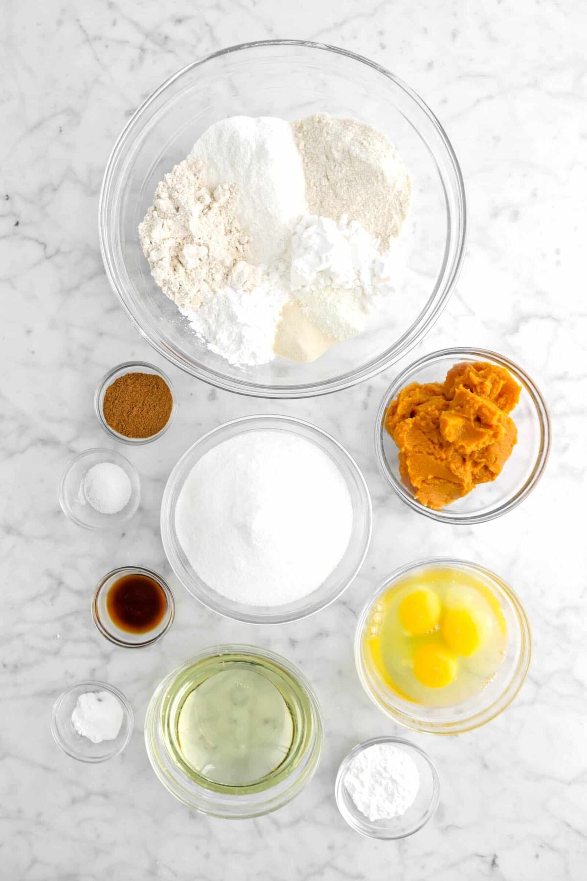 gluten free flours, pumpkin puree, sugar, spices, salt, vanilla, eggs, vegetable oil, baking powder, and baking soda in bowls on marble counter