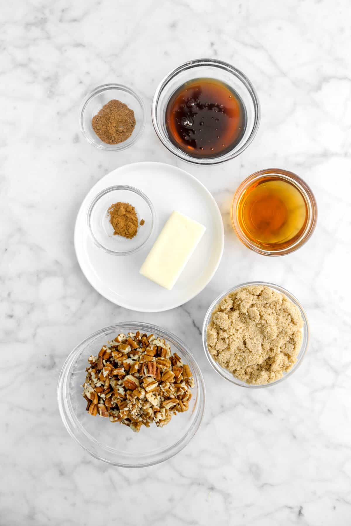 nutmeg, cinnamon, corn syrup, rum, butter, brown sugar, and chopped pecans on marble counter