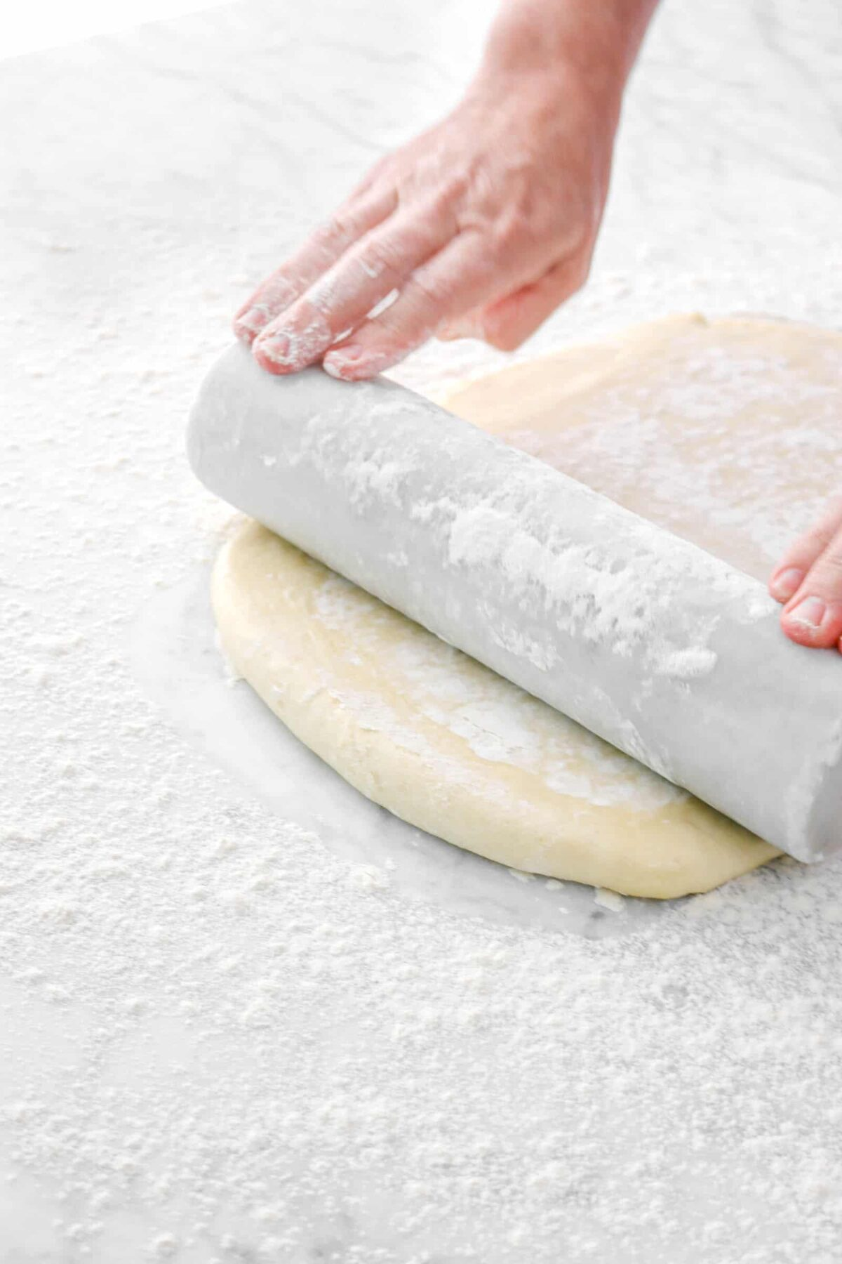 dough being rolled out with marble rolling pin
