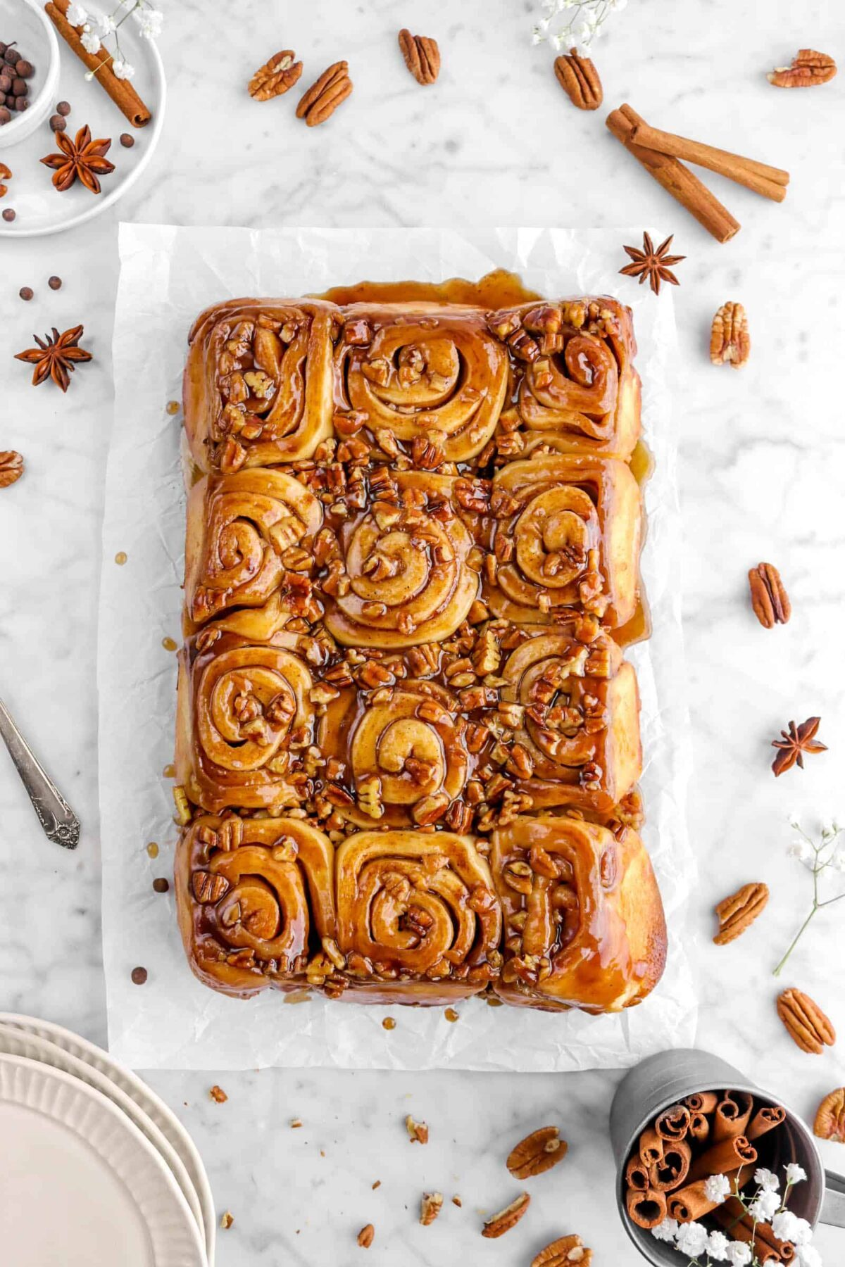 overhead shot of sticky buns on parchment with whole spices around