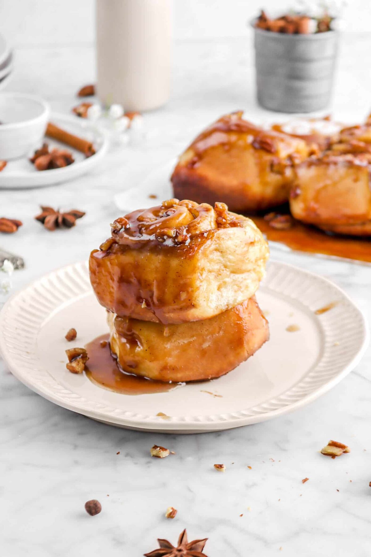 two stacked sticky buns on a white plate with more buns behind