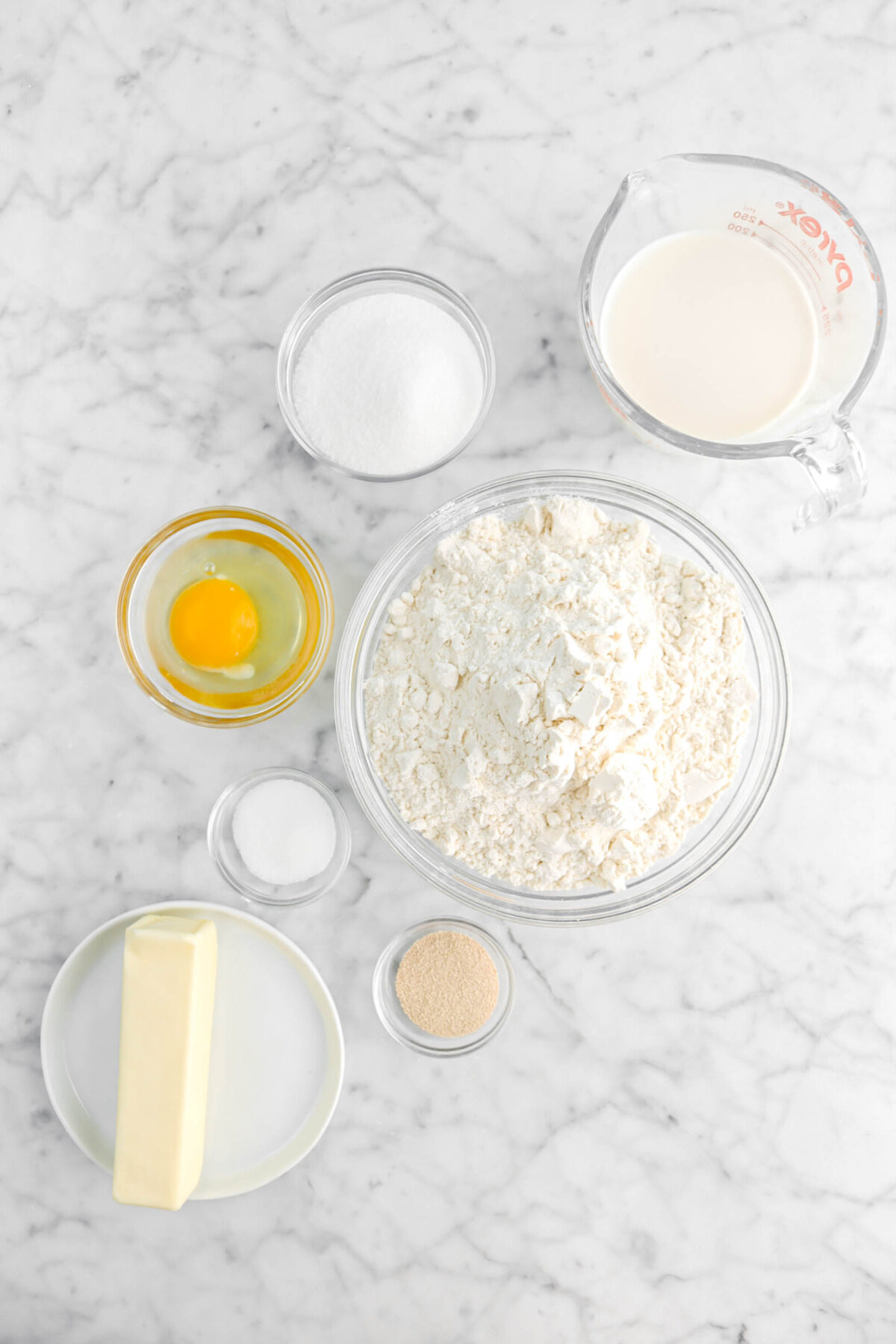 milk, sugar, egg, flour, salt, yeast, and butter on marble counter