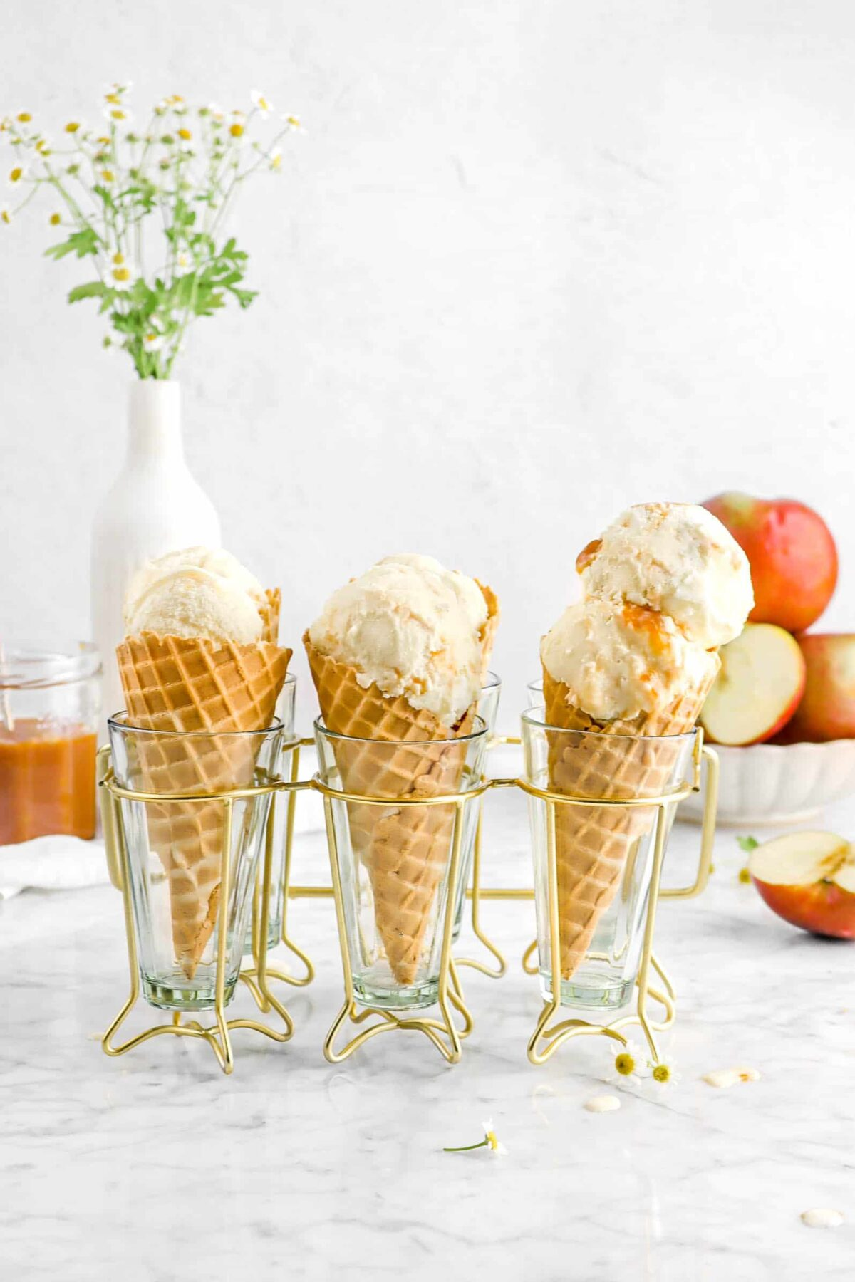 caramel apple ice cream in drink caddy with apples and flowers behind