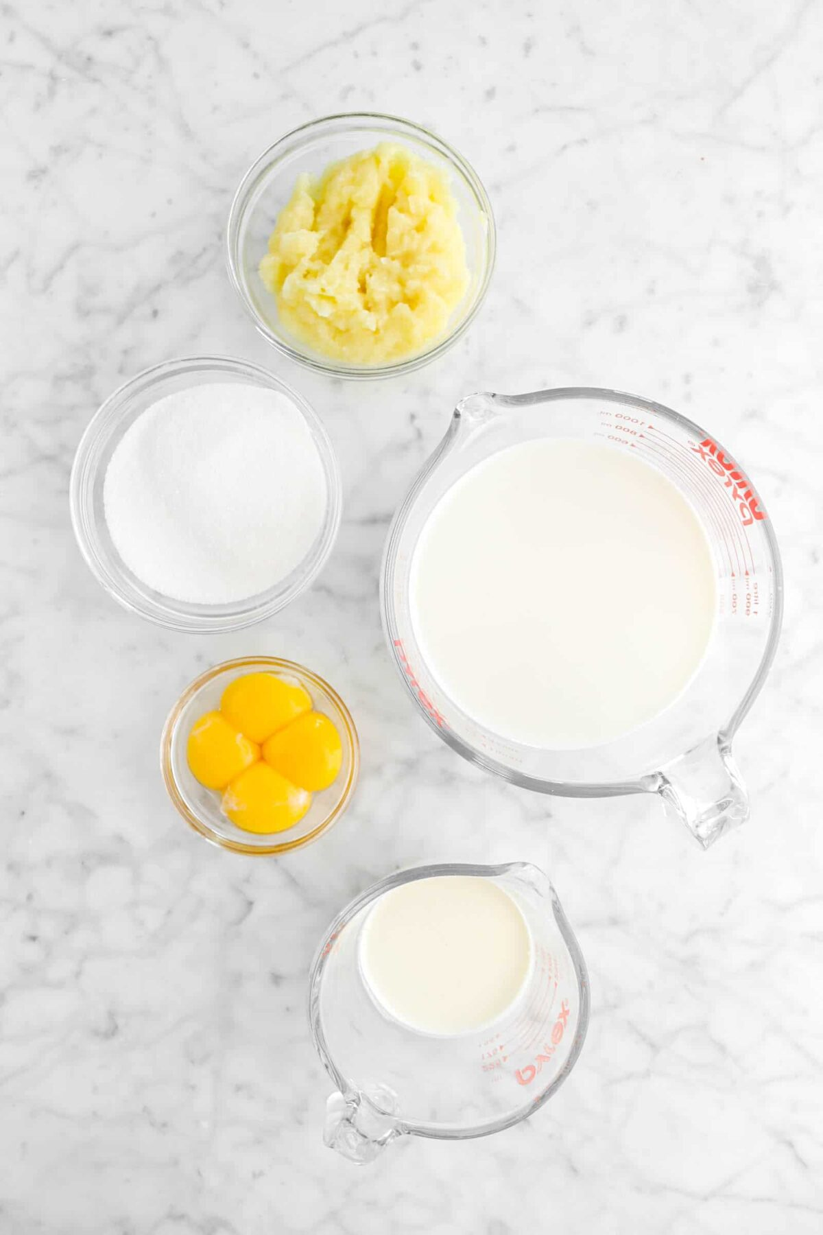 pureed apples, sugar, egg yolks, milk, and cream on marble counter