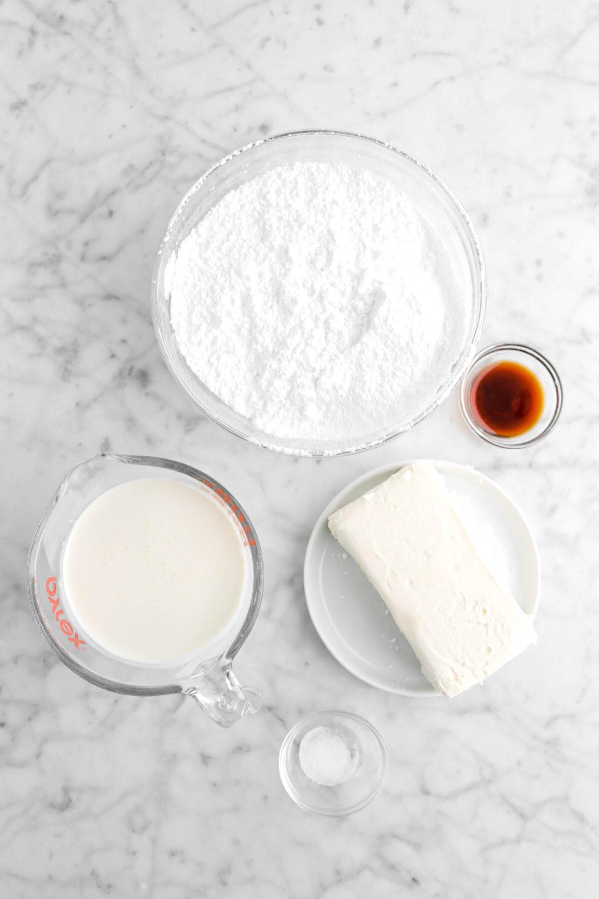 powdered sugar, vanilla, cream cheese, heavy cream, and salt on marble counter