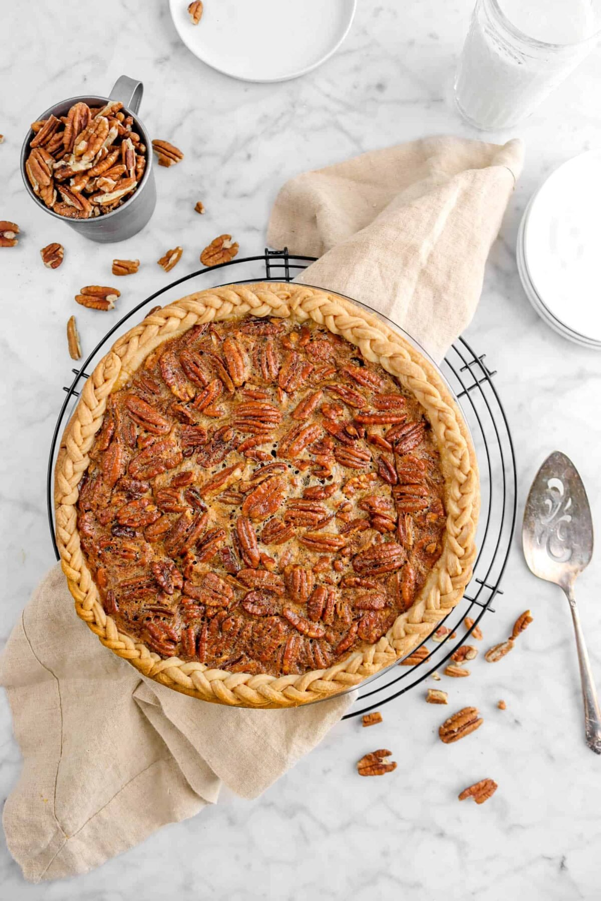 pecan pie on wire cooling rack with napkin and whole pecans
