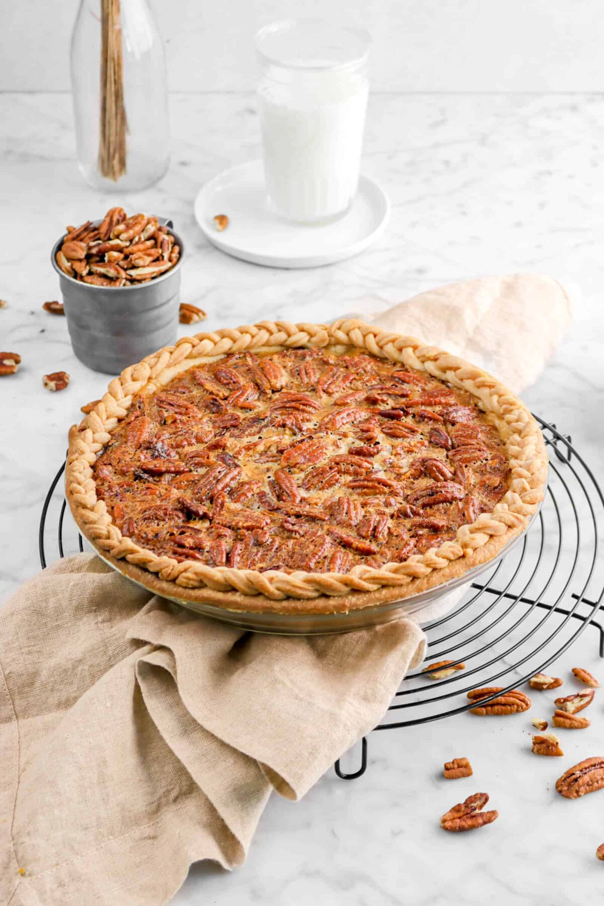 pecan pie on napkin with cup of whole pecans and glass of milk