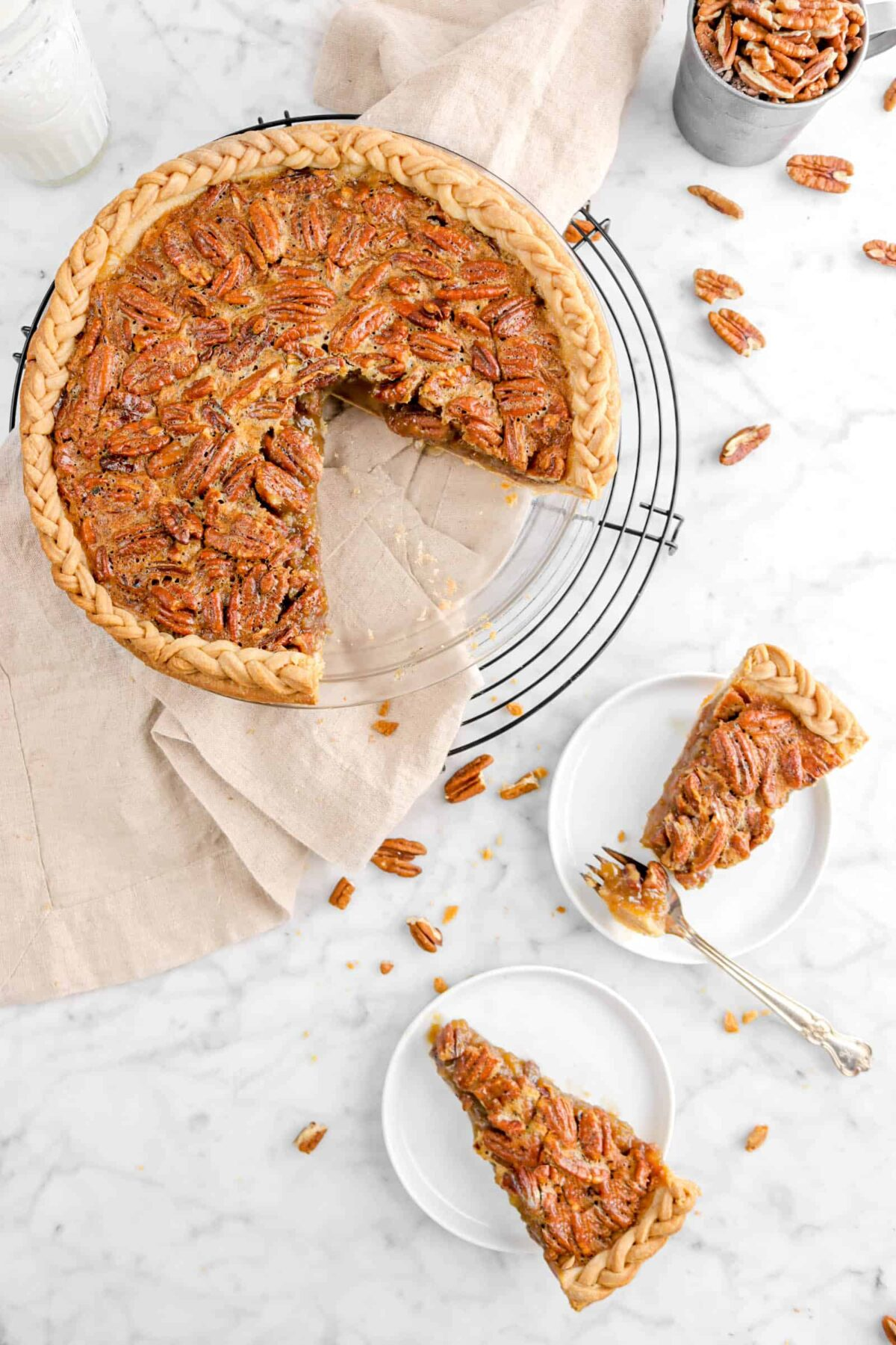 overhead shot of pecan pie with slices on white plate