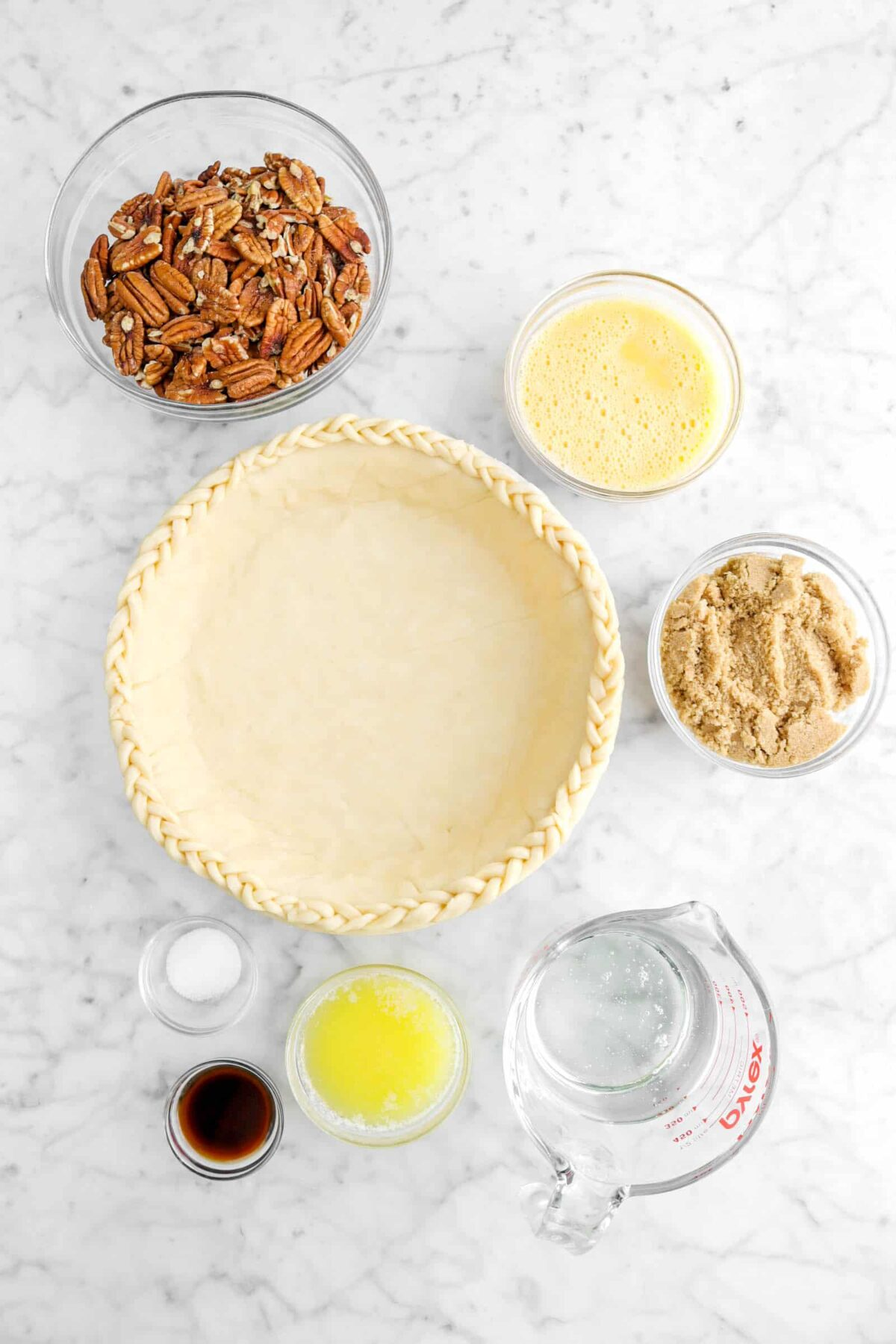 pecans, whisked eggs, pie crust, brown sugar, corn syrup, melted butter, salt, and vanilla on marble counter