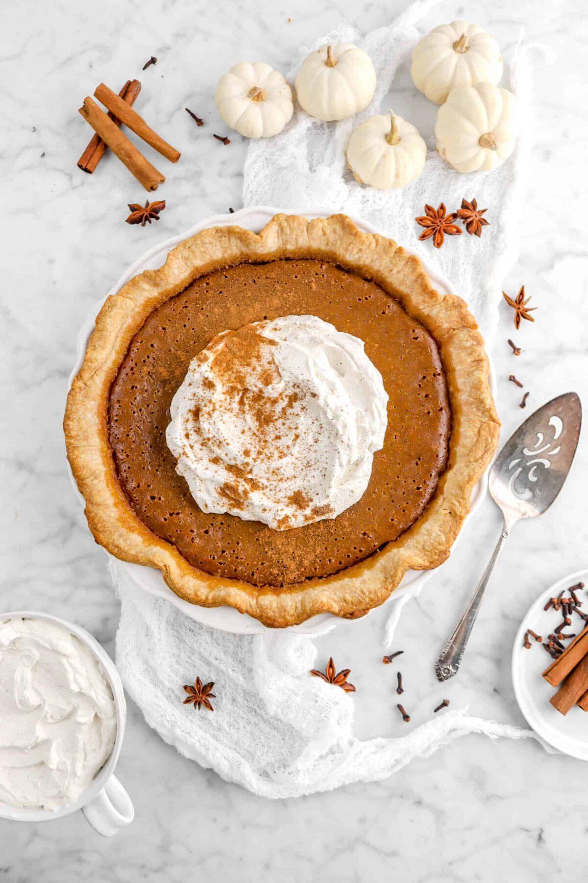 pumpkin pie on marble counter with mini pumpkins and whole spices