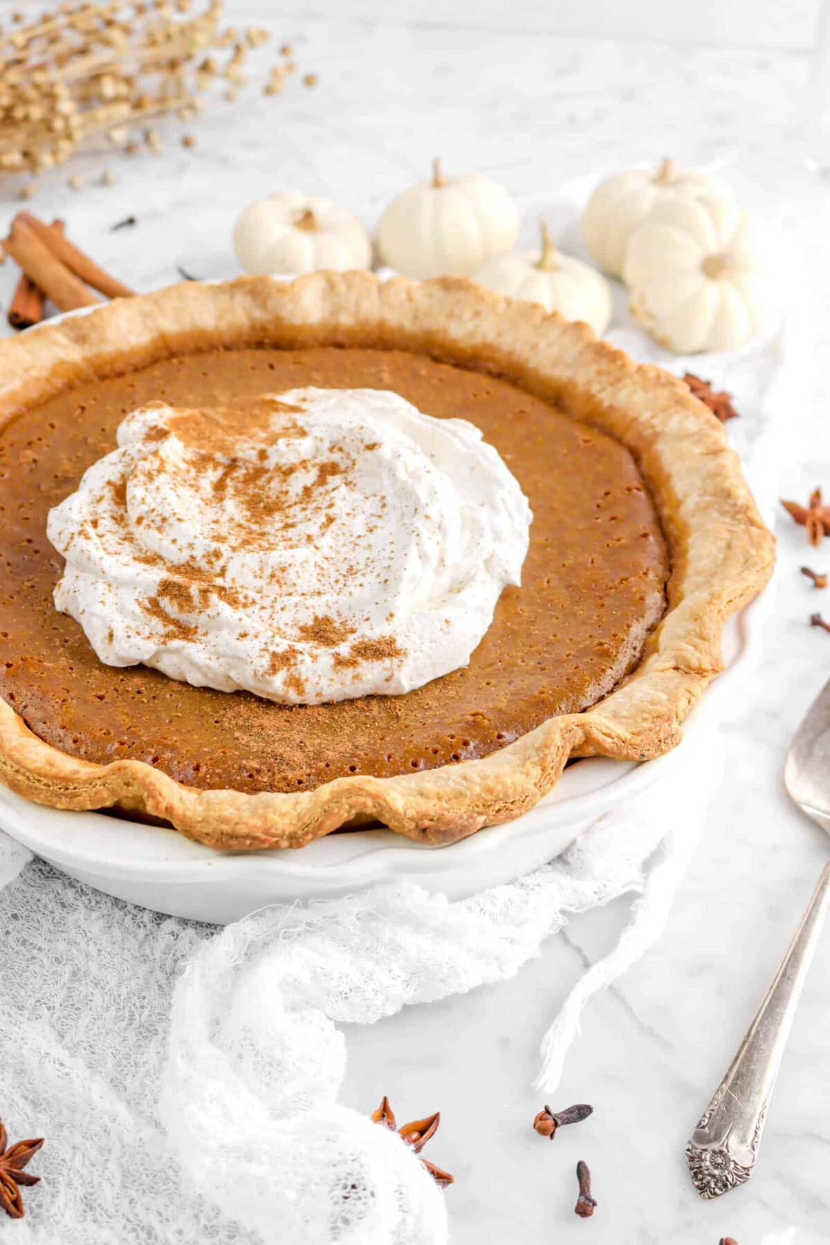 side shot of pumpkin pie on white cheese cloth with mini pumpkins behind