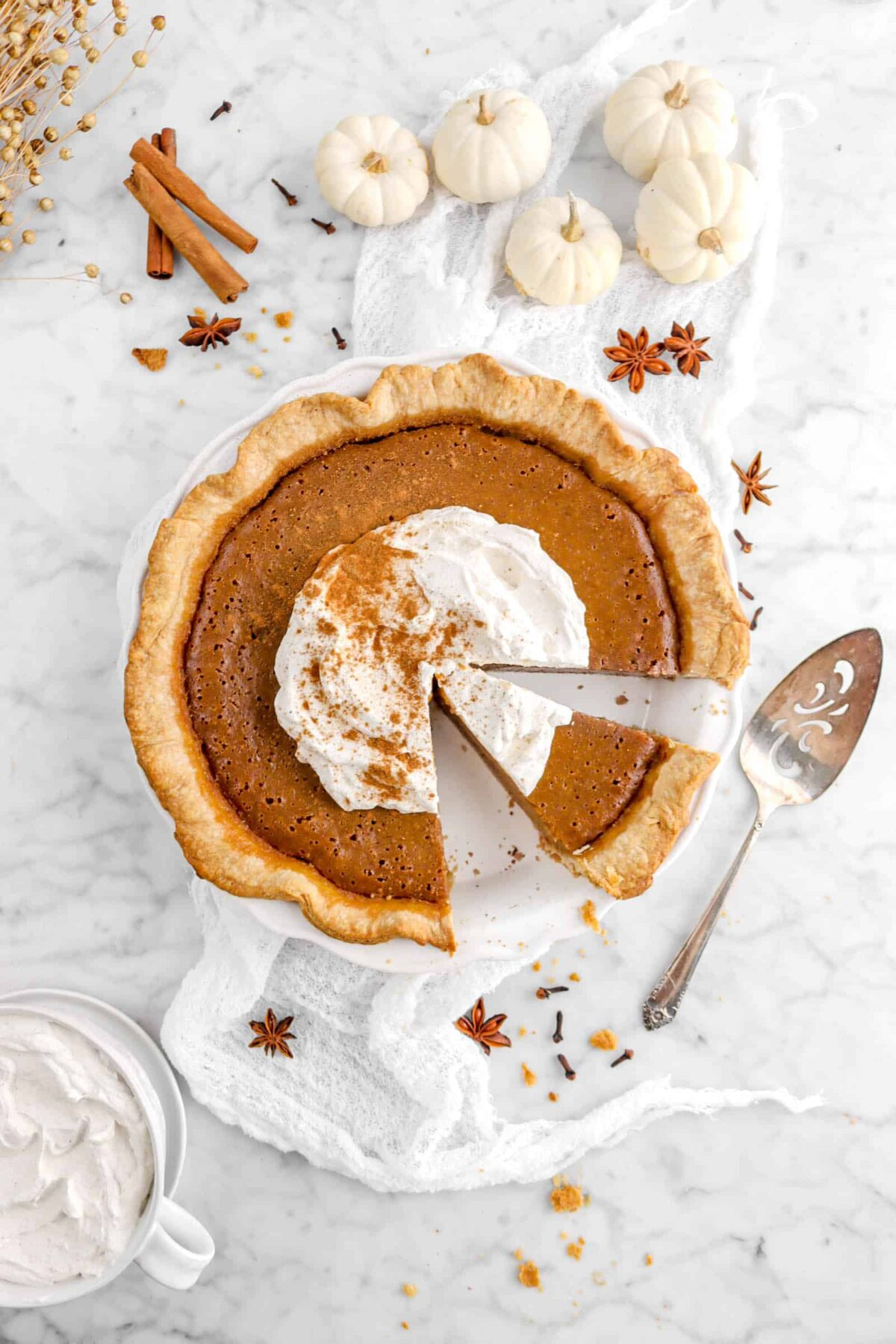 pumpkin pie cut with slice still in pie with whole spices and mini pumpkins around
