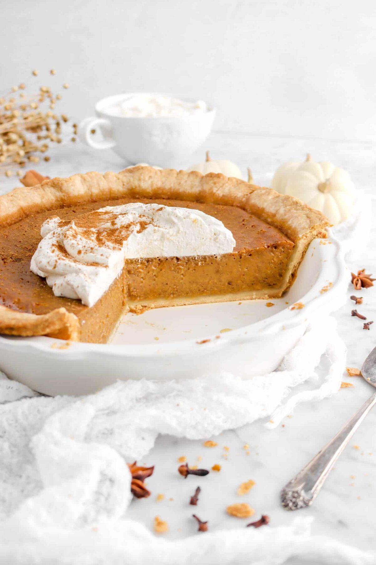 side shot of sliced pumpkin pie in pie plate