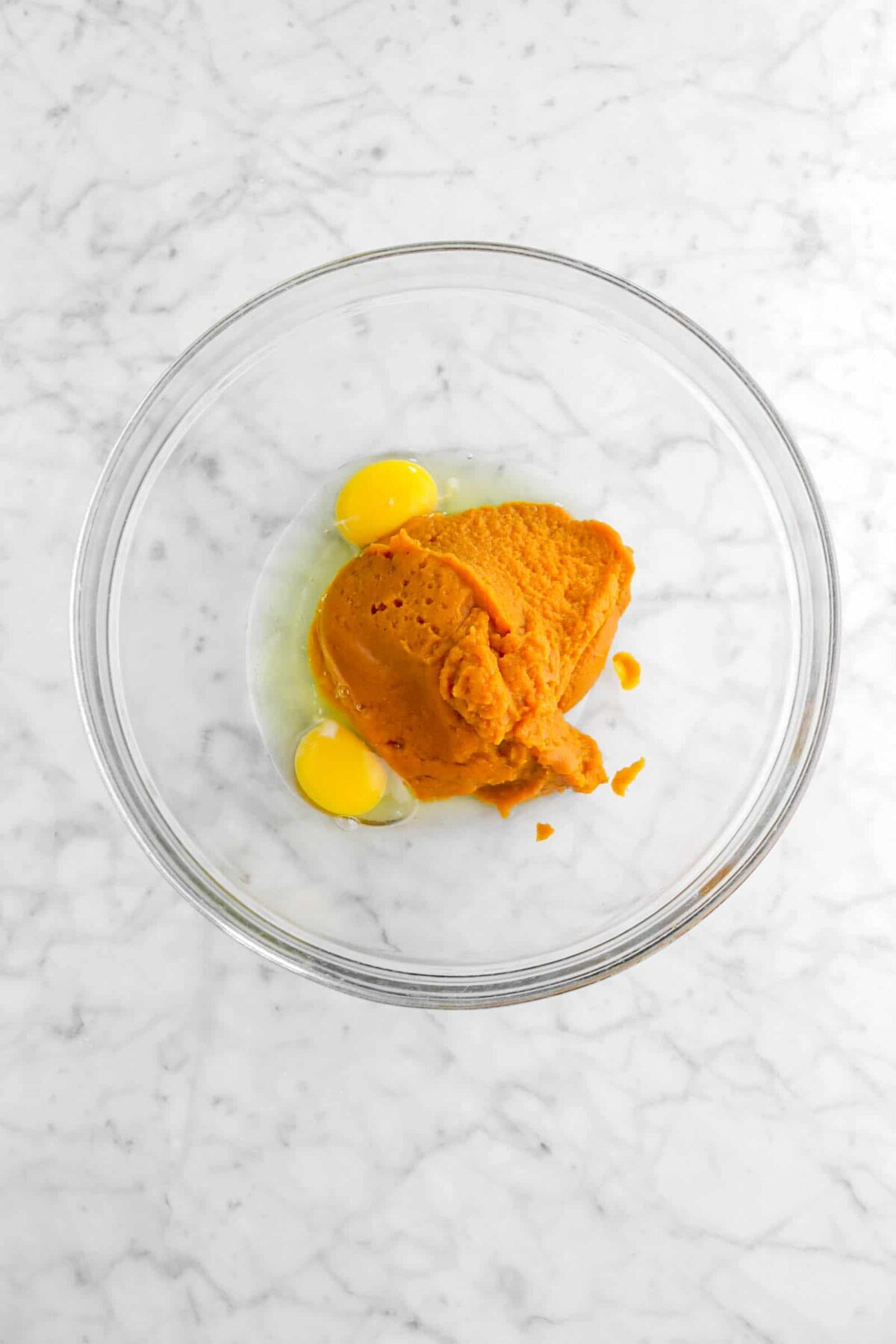 pumpkin puree and eggs in glass bowl