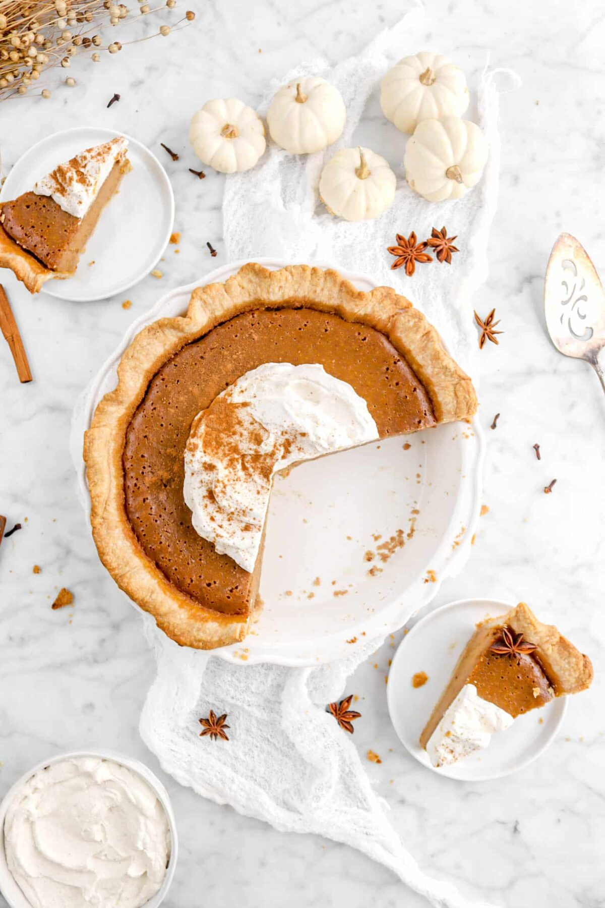 overhead shot of pumpkin pie with two slices on white plates, whole slices, and mini pumpkins