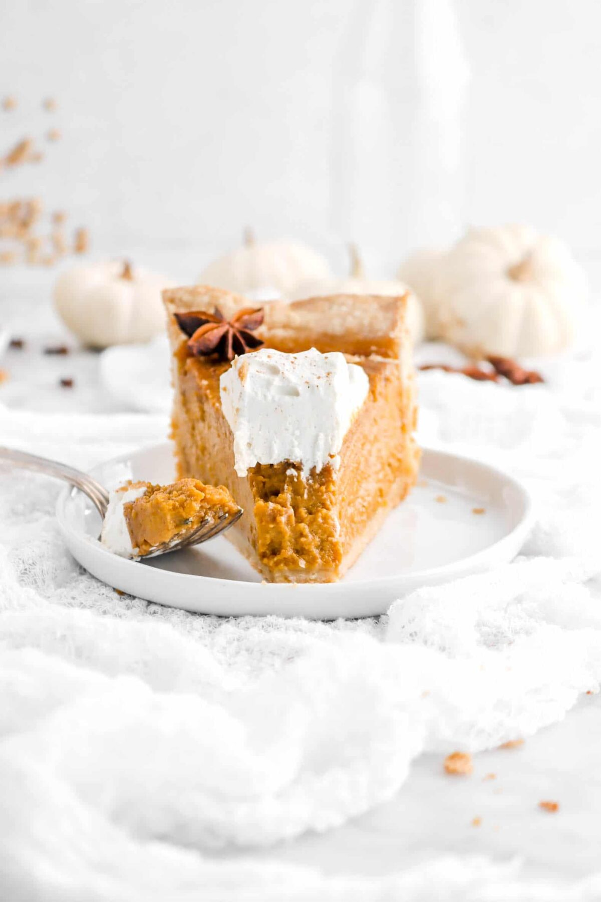pumpkin pie slice on white plate with fork and pumpkins behind